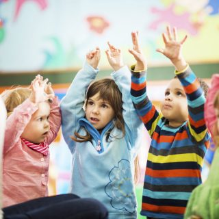 Cute children playing in the playroom with their arms raised.